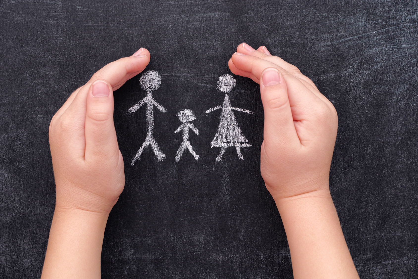 Child hands protecting family drawn on chalkboard. Family in hands.